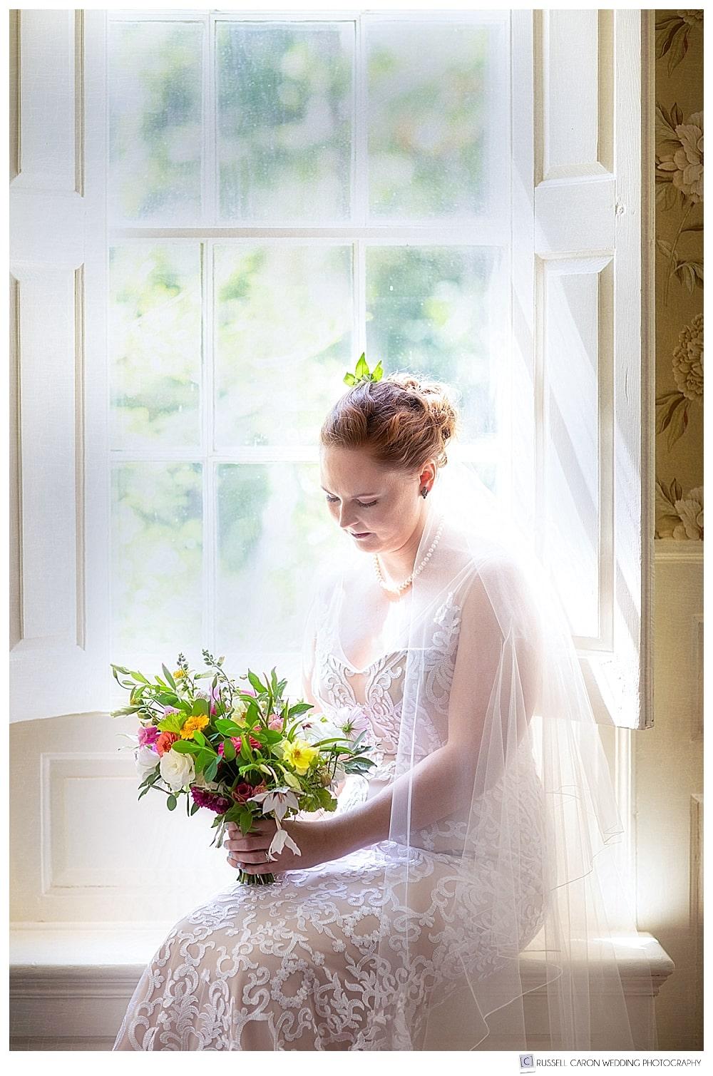 beautiful bridal portrait of bride sitting on a window seat at the 1774 Inn, Phippsburg, Maine