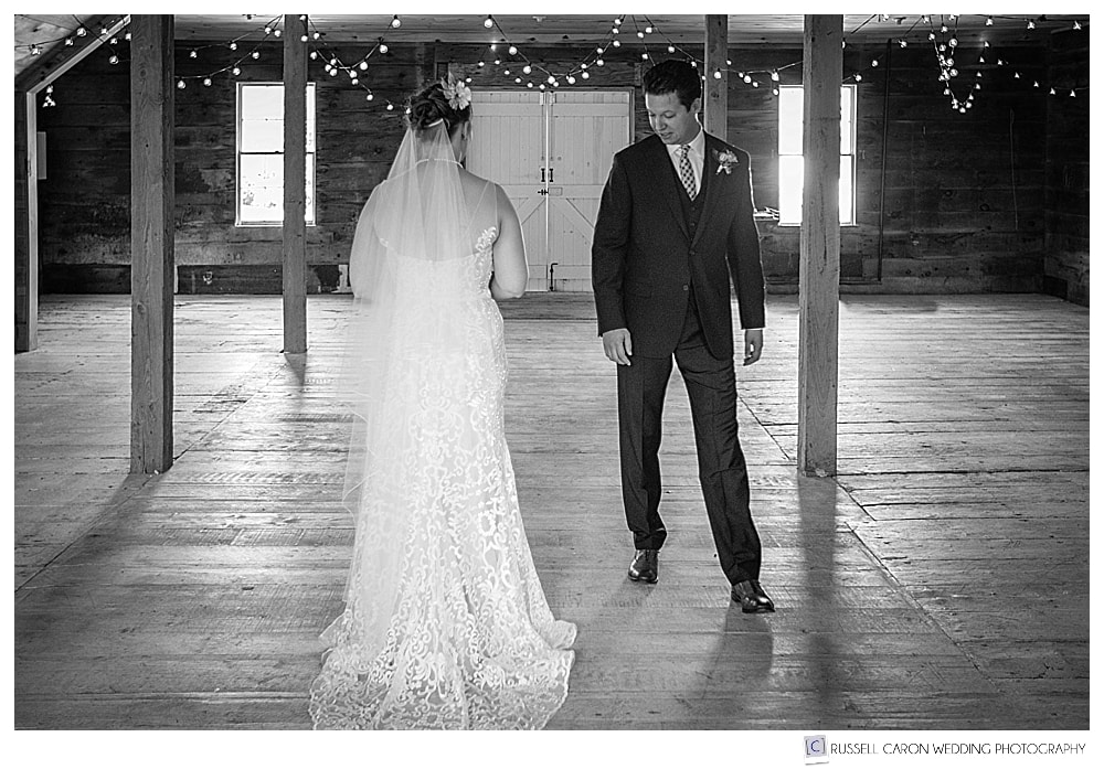 black and white photo of groom walking around bride, looking at her wedding dress