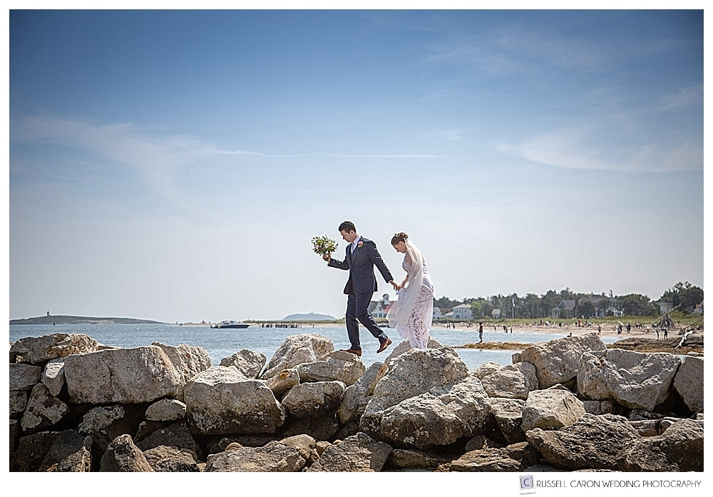 bride and groom walking along the top of the jetty at Fort Popham, Phippsburg, Maine