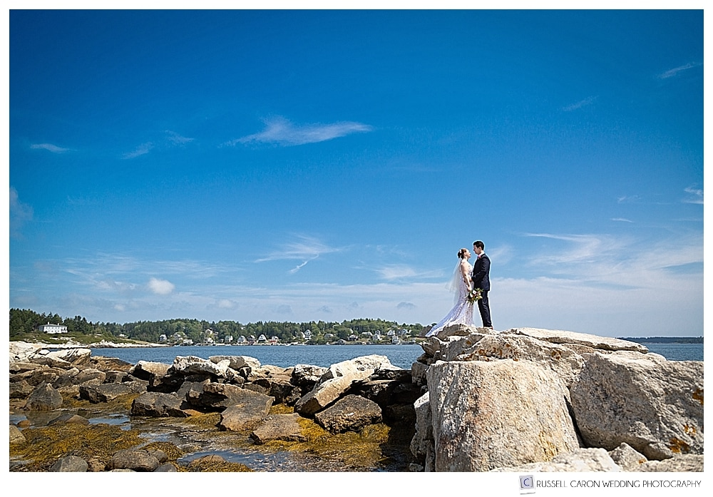 bride and groom standing at the end of the jetty at Fort Popham, Phippsburg, Maine