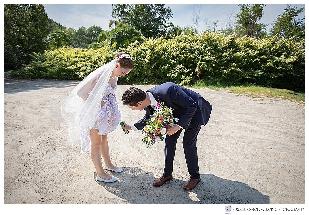 groom spraying bride with insect repellent