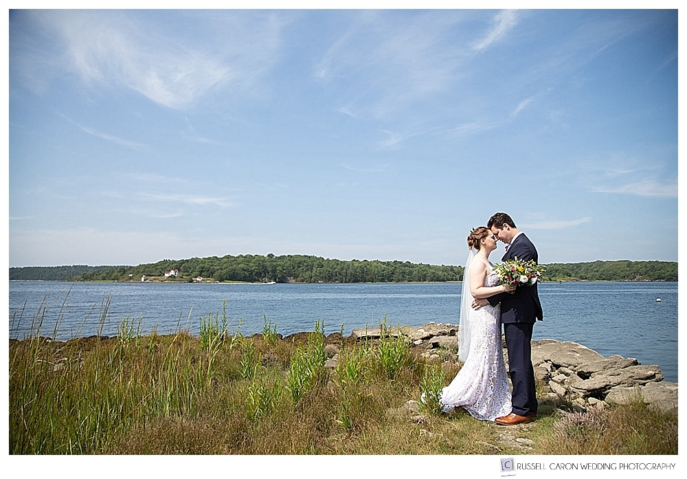 bride and groom standing on the banks of the Kennebec River in Phippsburg, Maine