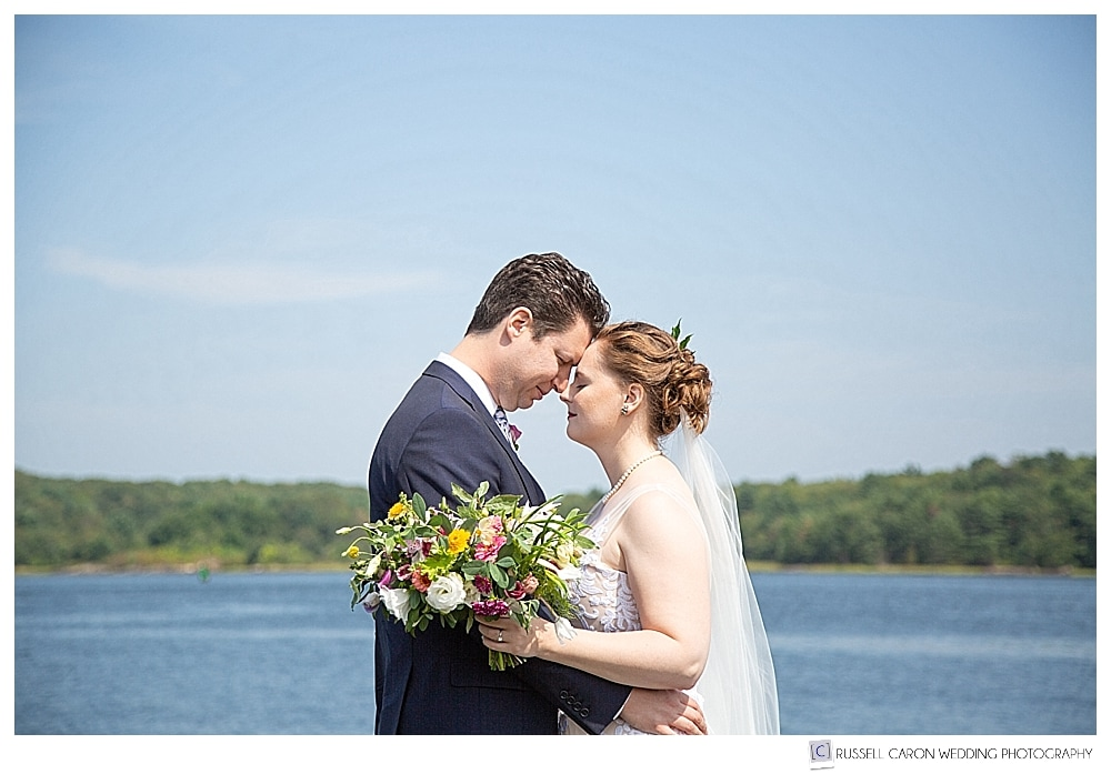 bride and groom standing together with foreheads touching, on the banks of the Kennebec River, Phippsburg, Maine