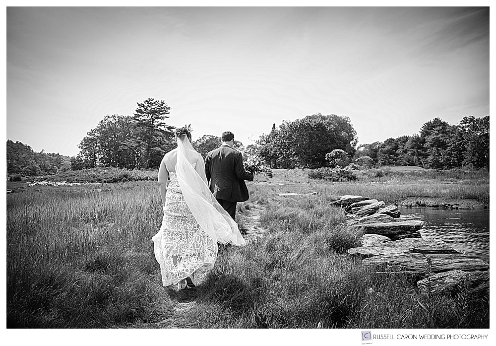 black and white photo of bride and groom walking through a marsh on the edge of the Kennebec River, Phippsburg, Maine