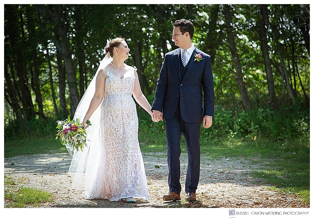 bride and groom standing side by side, holding hands and smiling at each other