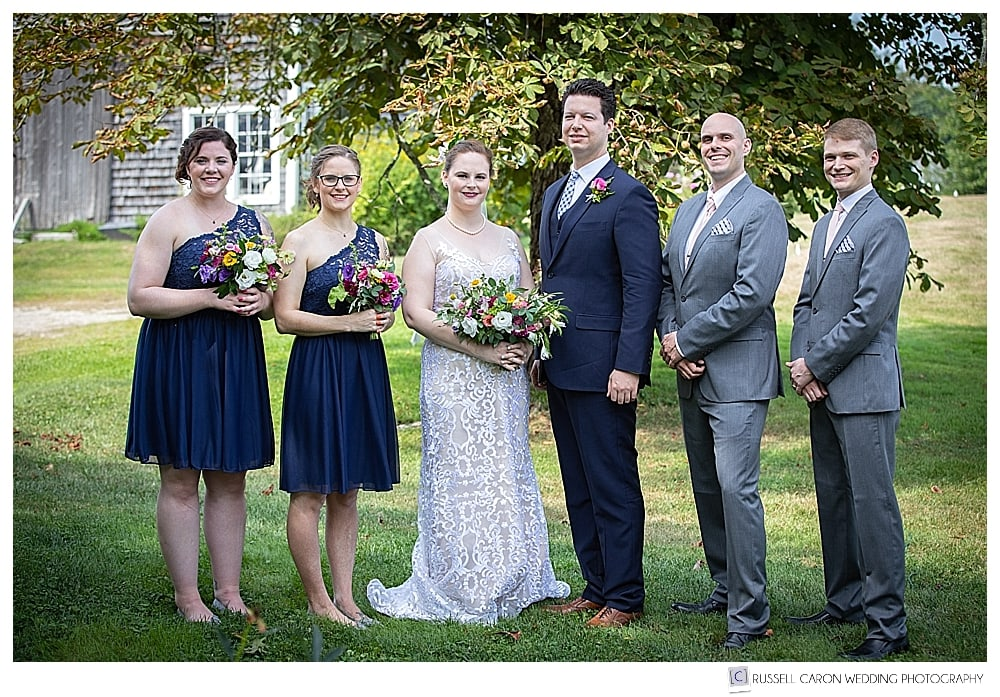 bride and groom with bridal party standing side by side