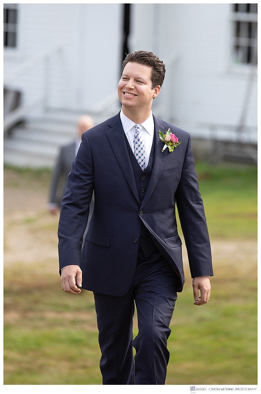 groom walking towards the outdoor ceremony site at the 1774 Inn, Phippsburg, Maine