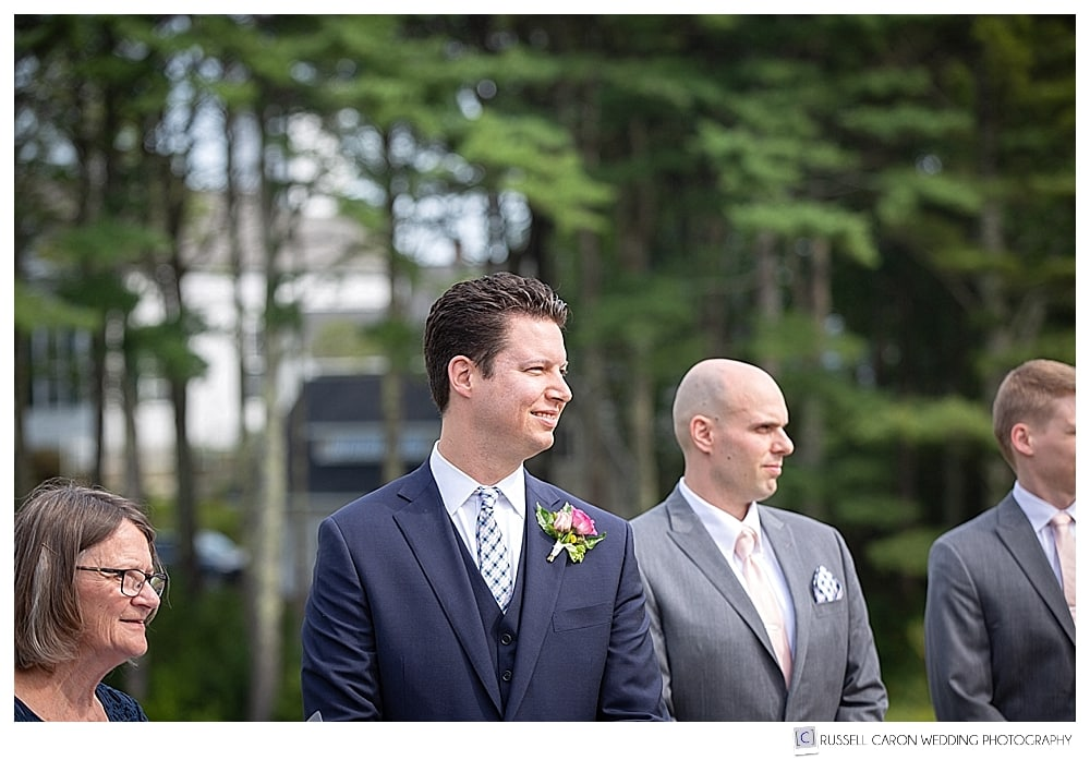 groom watches bride and her father walking toward him