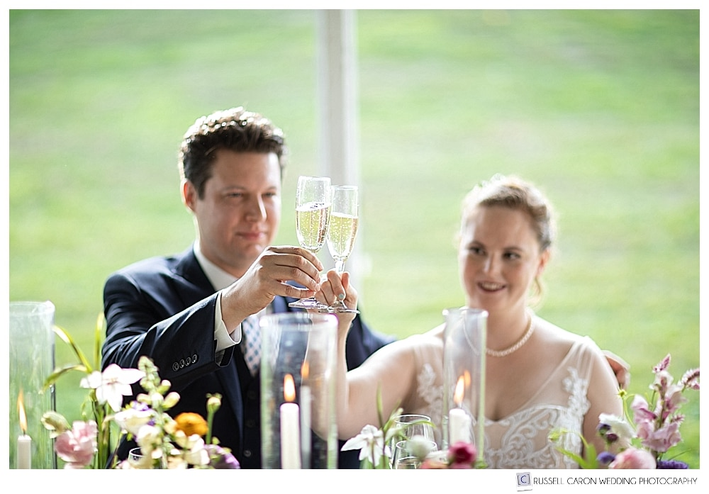 bride and groom toasting with champagne flutes, during their 1774 Inn wedding reception