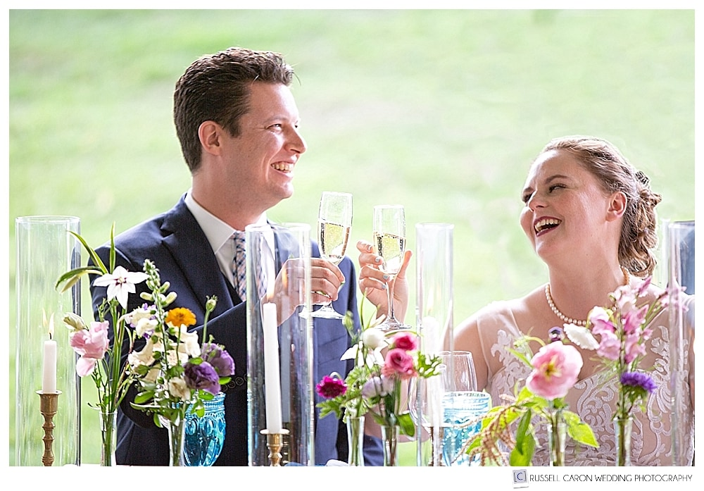 bride and groom laughing while toasting with champagne