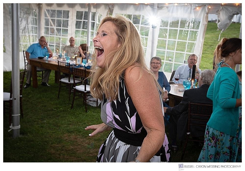 woman dancing under a reception tent