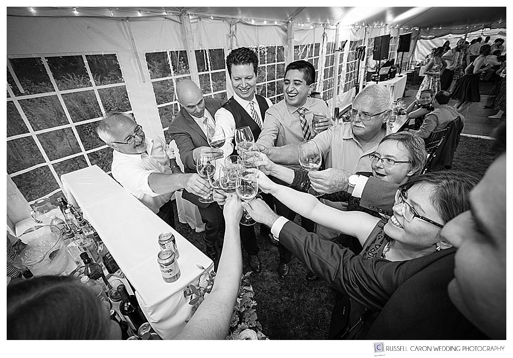 black and white photo of a group of people toasting each other with wine glasses