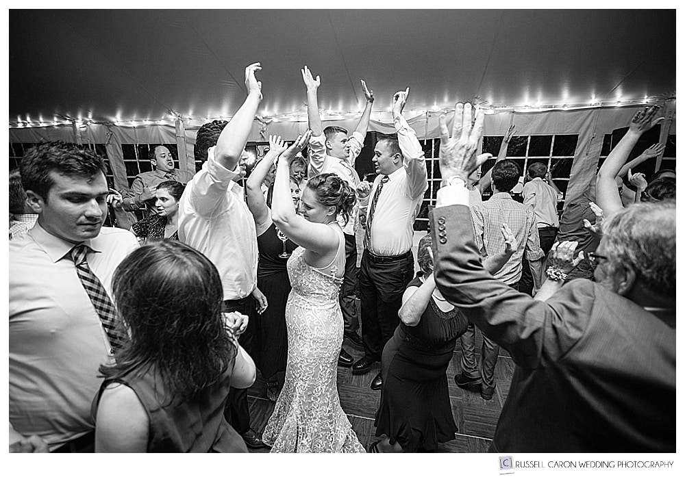 black and white photo of bride and groom dancing with guests