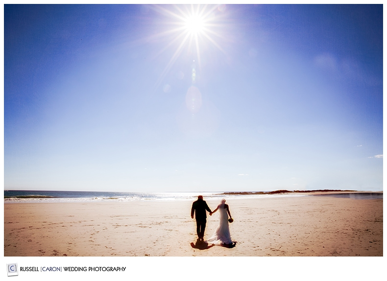 bride-and-groom-walking-hand-in-hand-on-beach