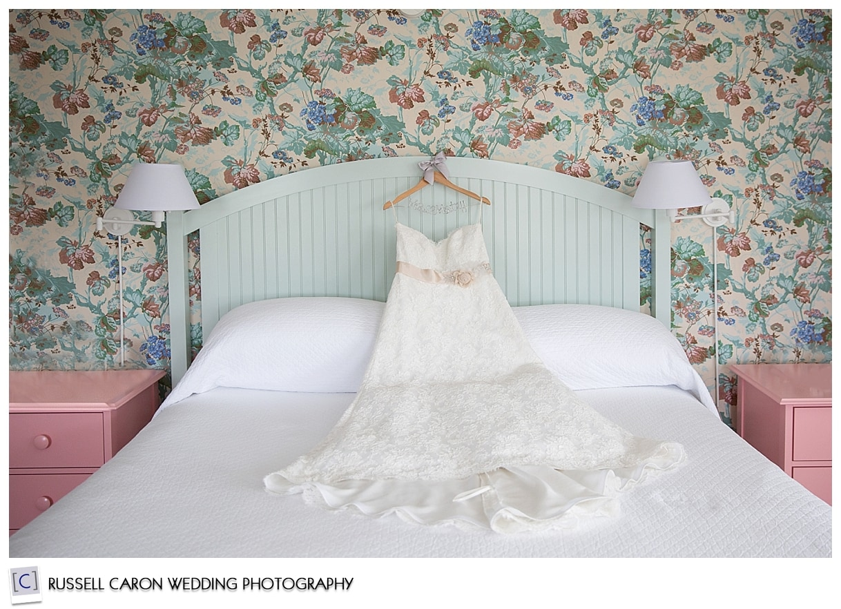Wedding gown draped over bed