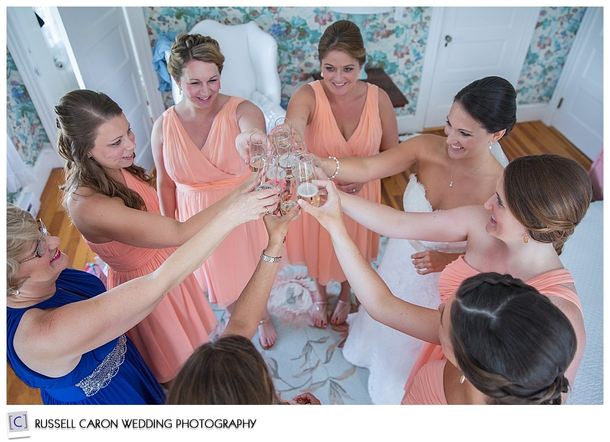 Bride and bridesmaid toasting with champagne