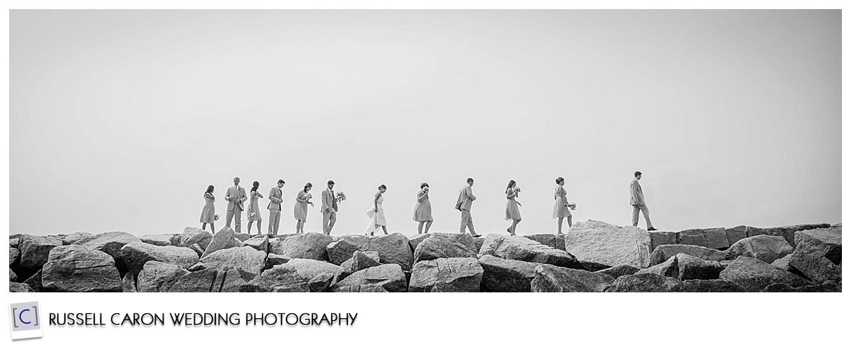 Bridal party walking on breakwater in Kennebunkport
