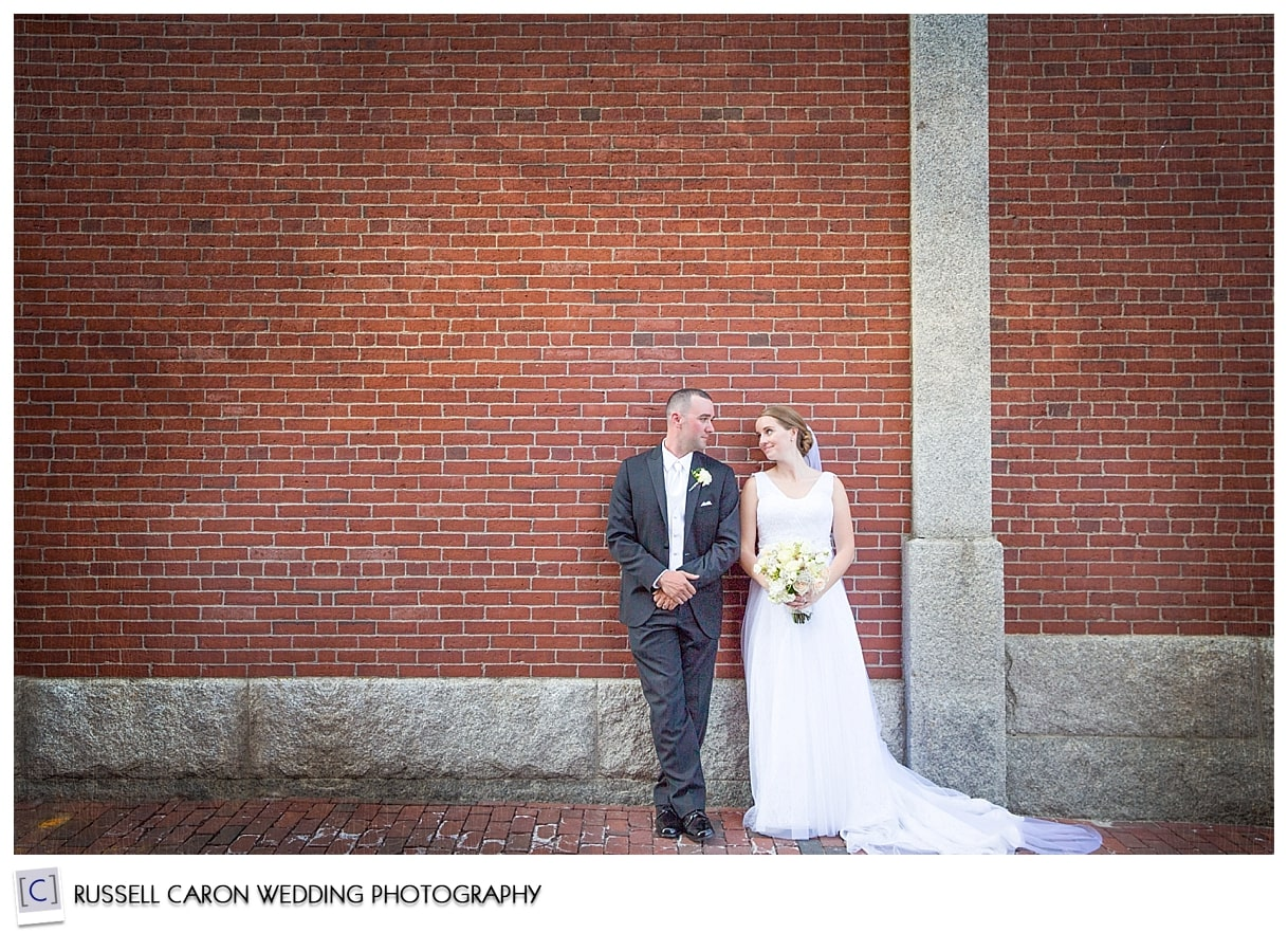 Bride and groom in front of brick wall in Portland Maine, by Portland Maine wedding photographers, Russell Caron Wedding Photography