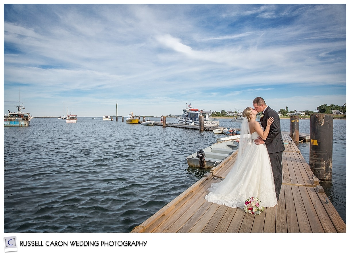 Couple kissing on dock in Pine Point Scarborough Maine, by Scarborough Maine wedding photographers Russell Caron Wedding Photography