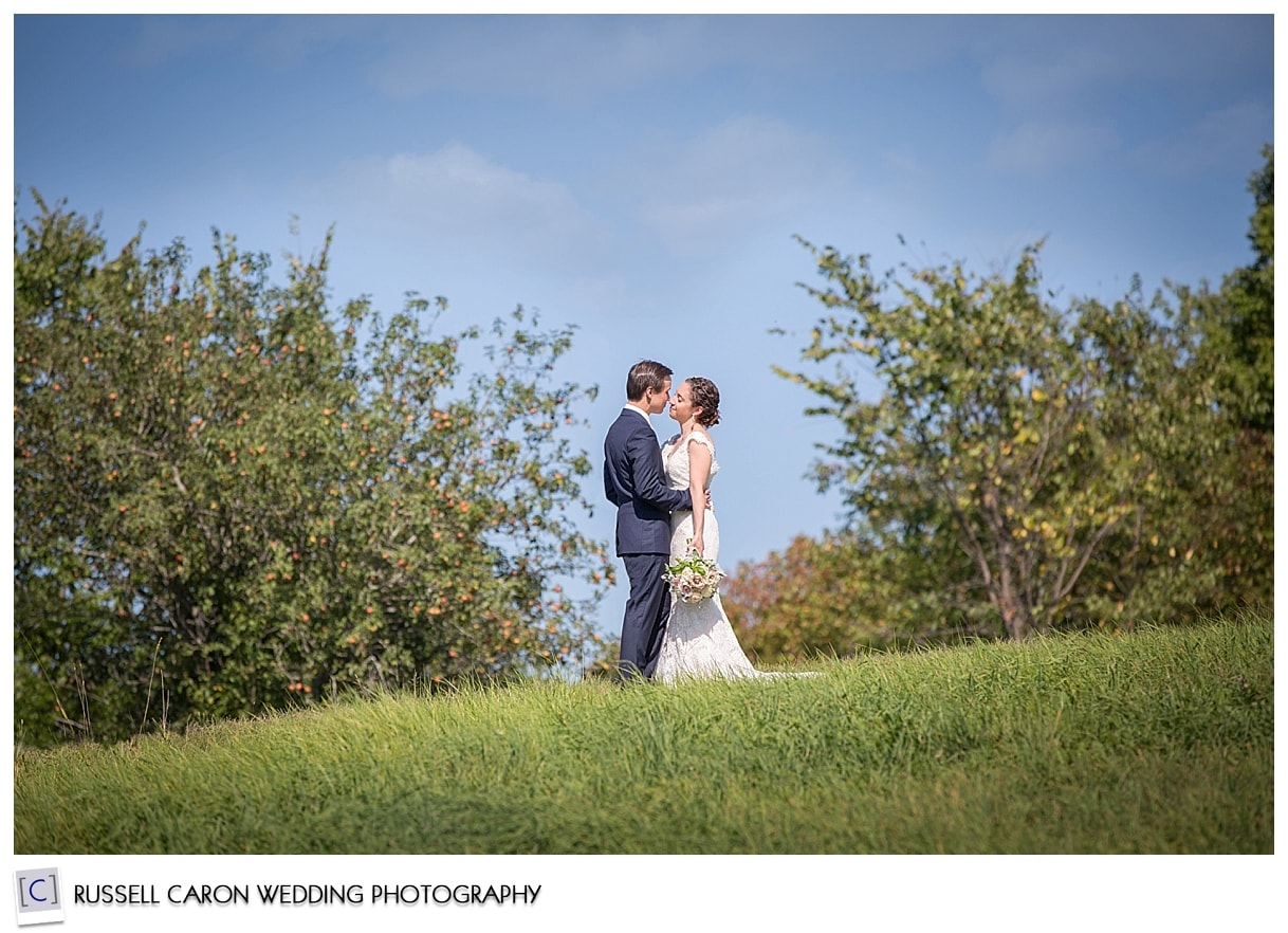 Bride and groom in field at Pineland Farms New Gloucester Maine, by Pineland Farms Maine wedding photographers, Russell Caron Wedding Photography