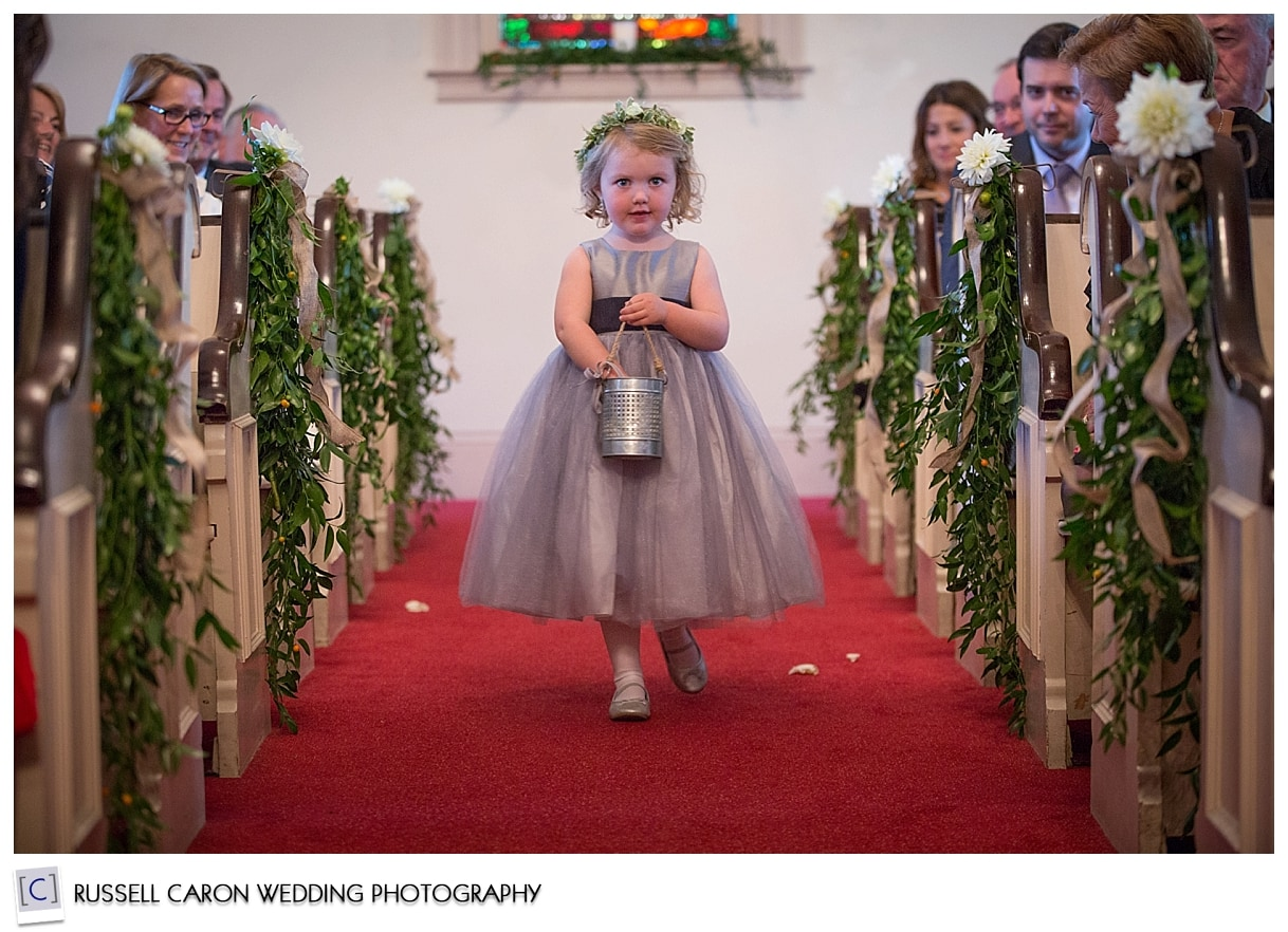 Flower girl walking down aisle at South Congregational Church, Kennebunkport, Maine