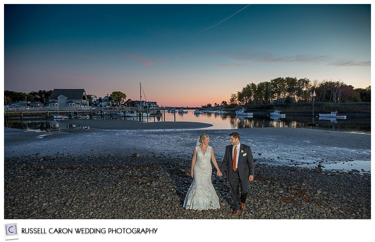bride-and-groom-walking-hand-in-hand-during-sunset