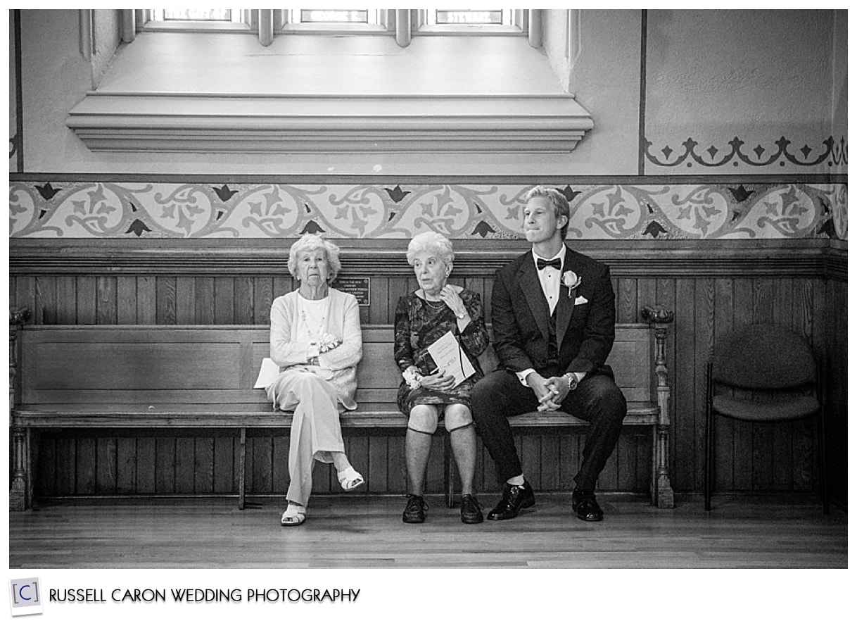 Best man and grandmothers sitting on bench at back of the church