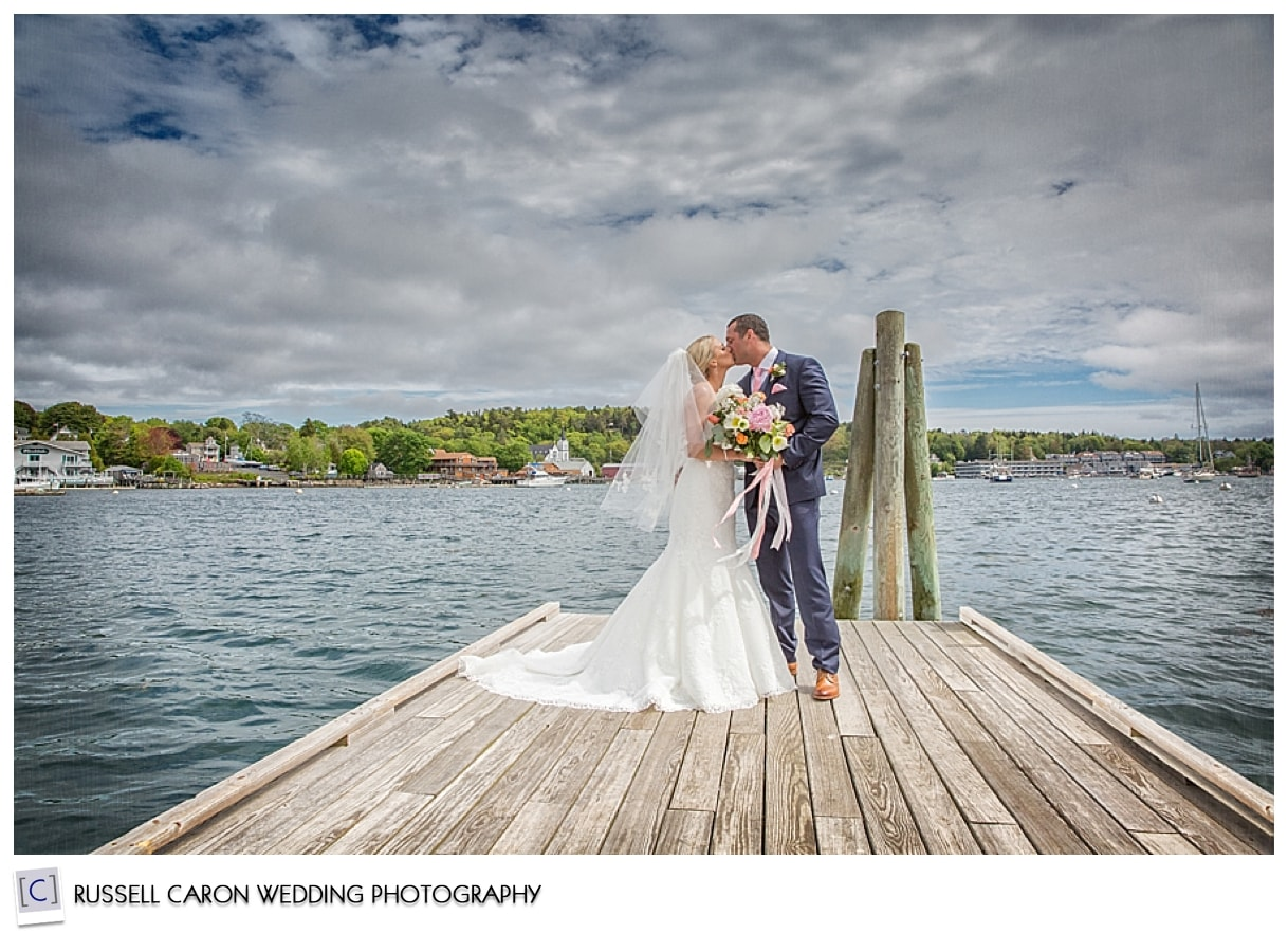Bride and groom kissing on dock in Boothbay Maine