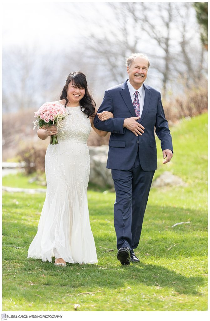 bride and her dad walk down outdoor aisle