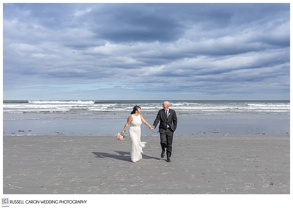 couple walks at the beach right after being married