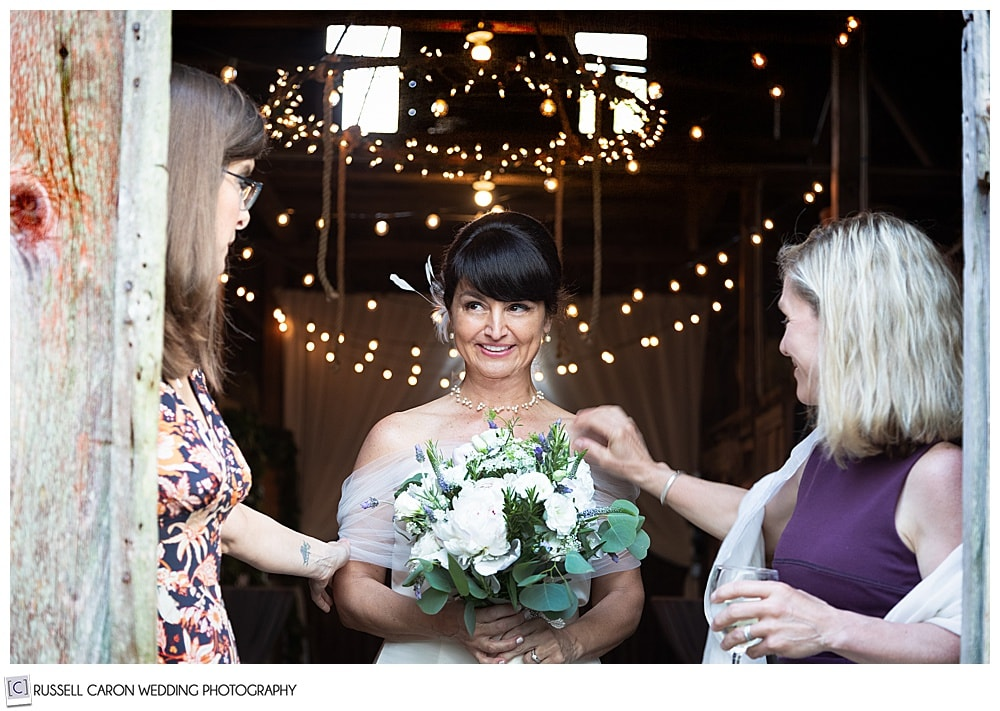 A pensive bride stands with two friends