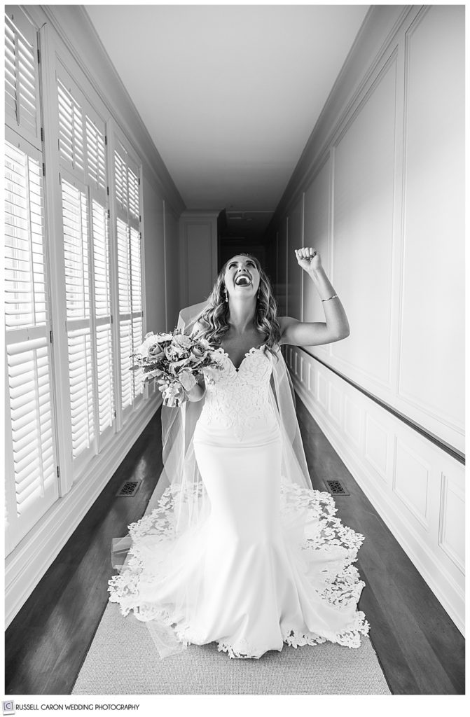black and white photo ecstatic bride image standing in a hallway
