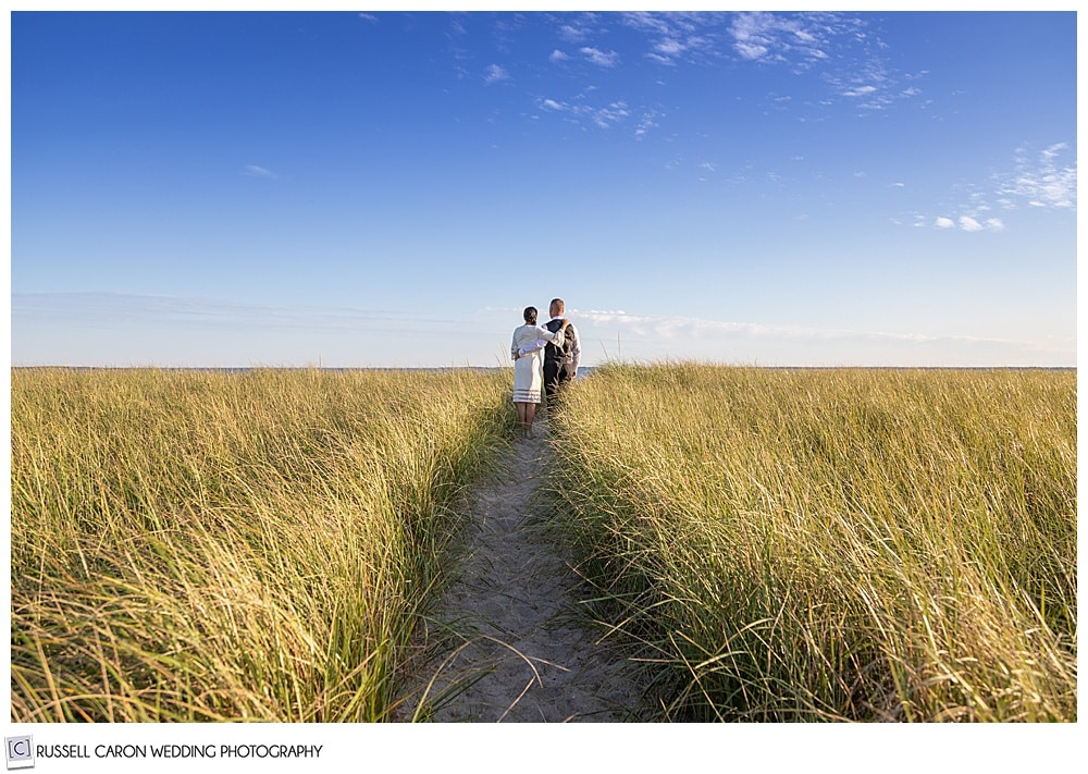 seaside elopement photo of a bride and groom walking through the sand dunes at Pine Point Beach, Scarborough, Maine