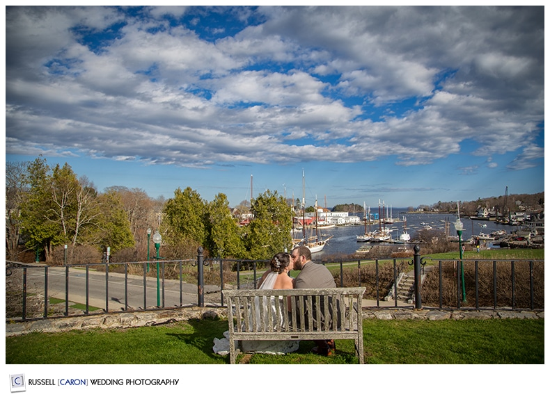 Bride and groom on a bench overlooking Camden Harbor Maine
