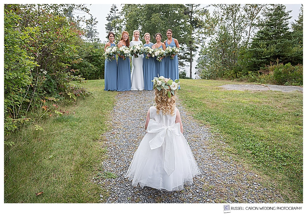 adorable flower girl photo, flower girl looking at bride and bridesmaids