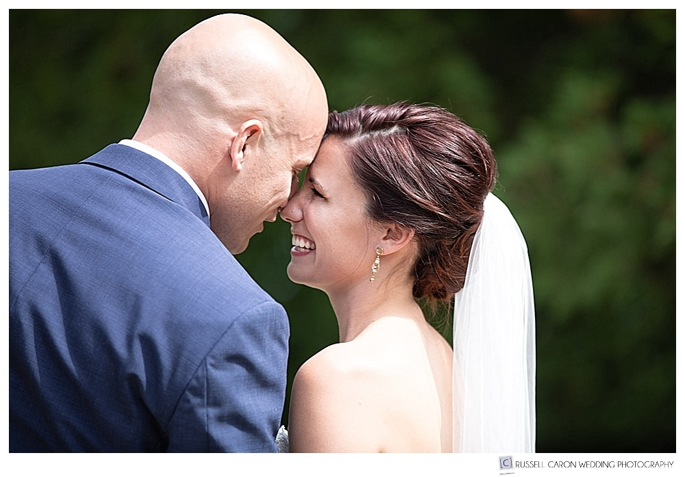 bride and groom touch foreheads during wedding day first look photos at College of the Atlantic, Bar Harbor, Maine