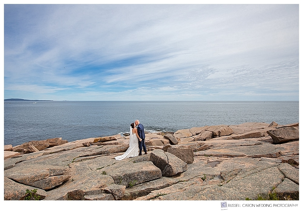 bride and groom kissing on the pink granite shore at Acadia National Park, Bar Harbor, Maine