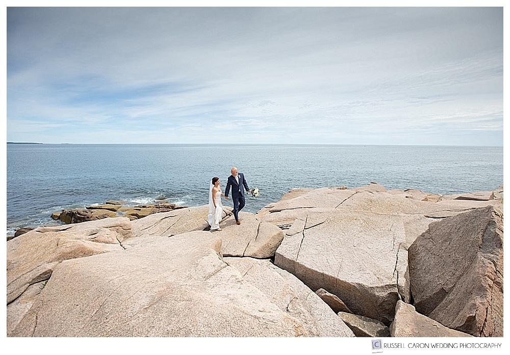 Bride and groom walking along the pink granite at Acadia National Park, Bar Harbor, Maine