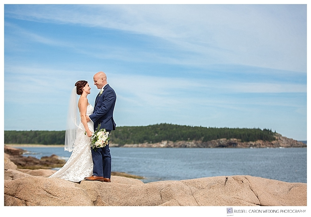 bride and groom standing together on the pink granite cliffs of Acadia National park, Bar Harbor, Maine