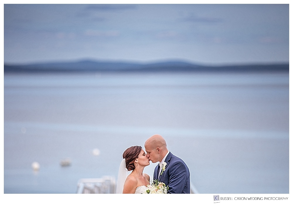 bride and groom kissing on the dock at their Atlantic Oceanside Bar Harbor wedding, Bar Harbor, Maine