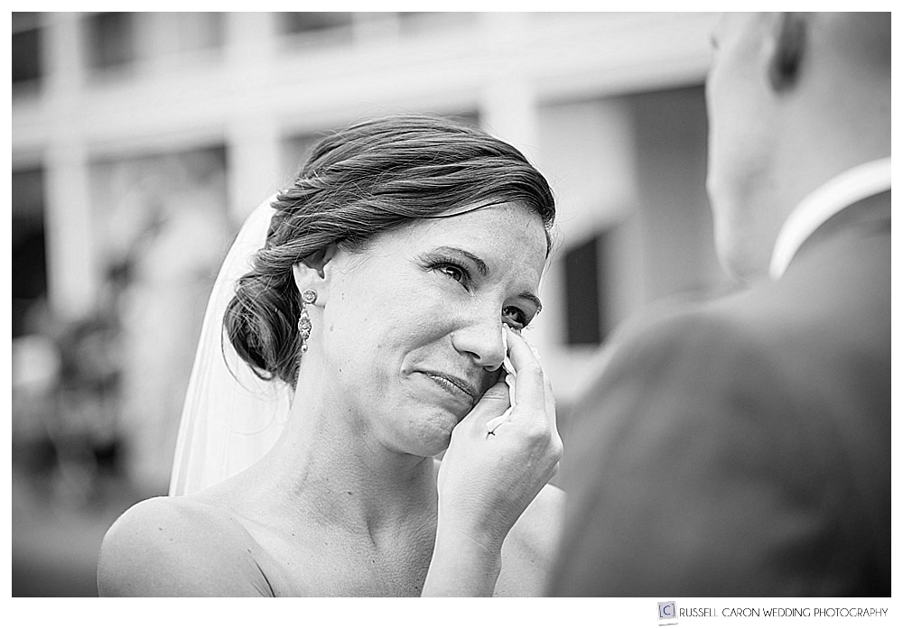 black and white photo of bride wiping a tear