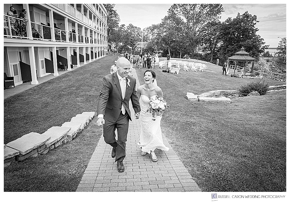 black and white photo of the bride and groom walking and laughing at the Atlantic Oceanside Resort, Bar Harbor, Maine