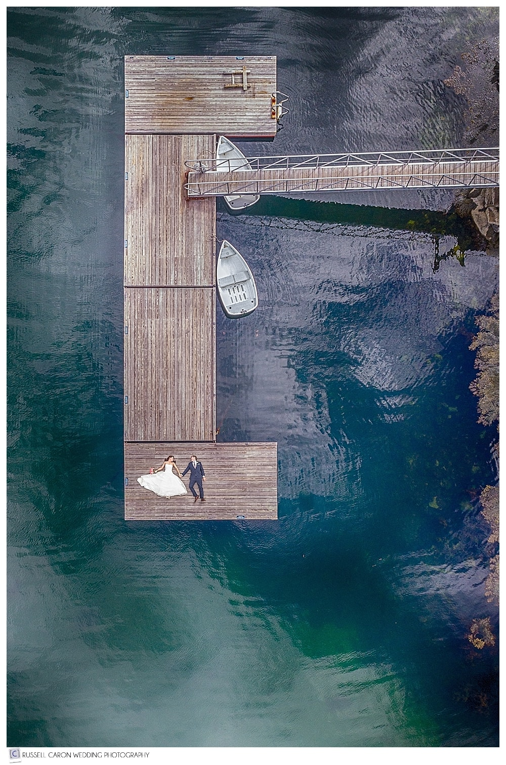 Maine Drone wedding photos, by Maine drone wedding photographers capture a drone photo of a bride and groom on the dock at their Newagen Seaside Inn wedding in Southport Maine weddings