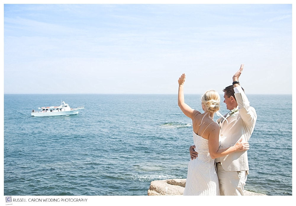 bride and groom wave to boat off of bar harbor maine