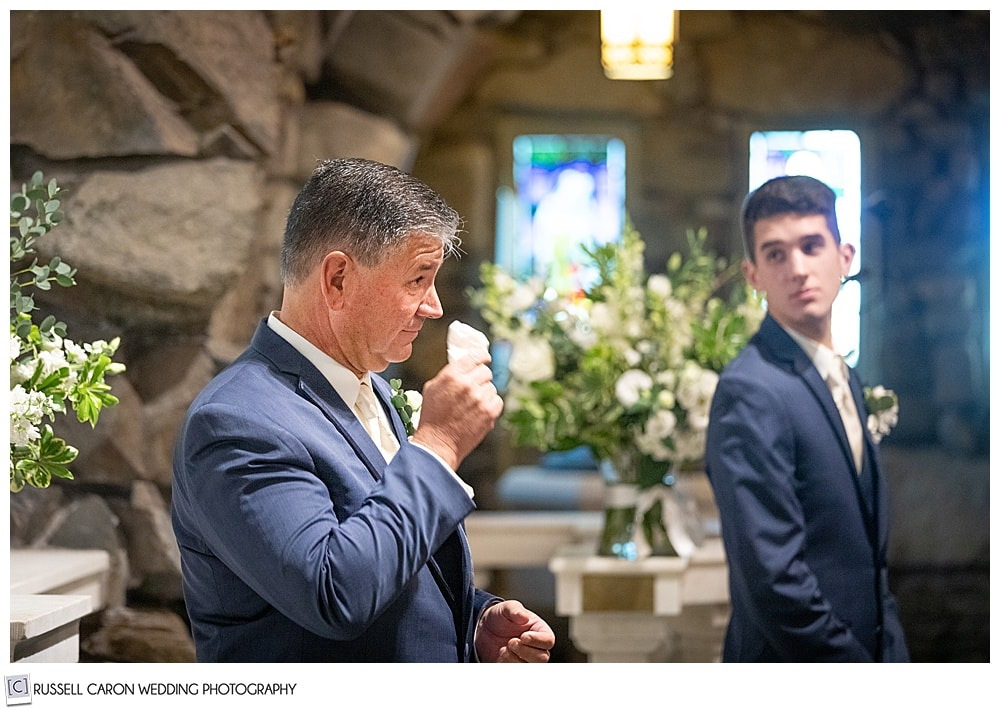a groom, standing before the altar at St. Ann's Episcopal Church, Kennebunkport, Maine, hie's dabbing at his eyes with a handkerchief, his son is turning to look at him