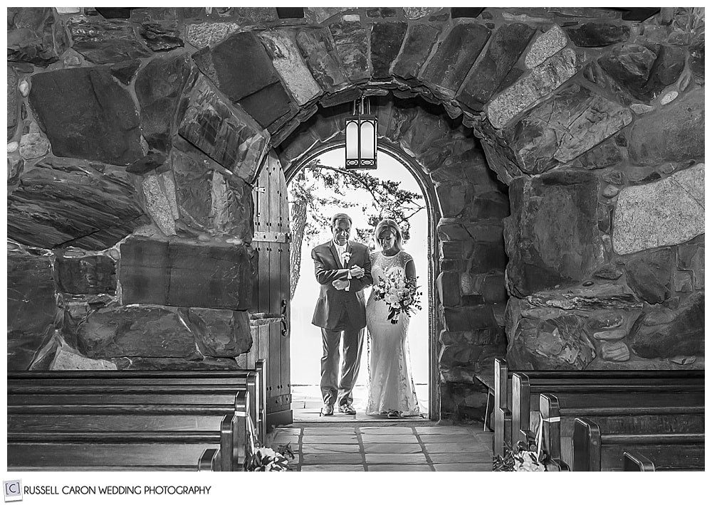 black and white photo of a bride and her father entering Saint Ann's Episcopal Church, Kennebunkport, Maine, to walk down the aisle to the groom who awaits them