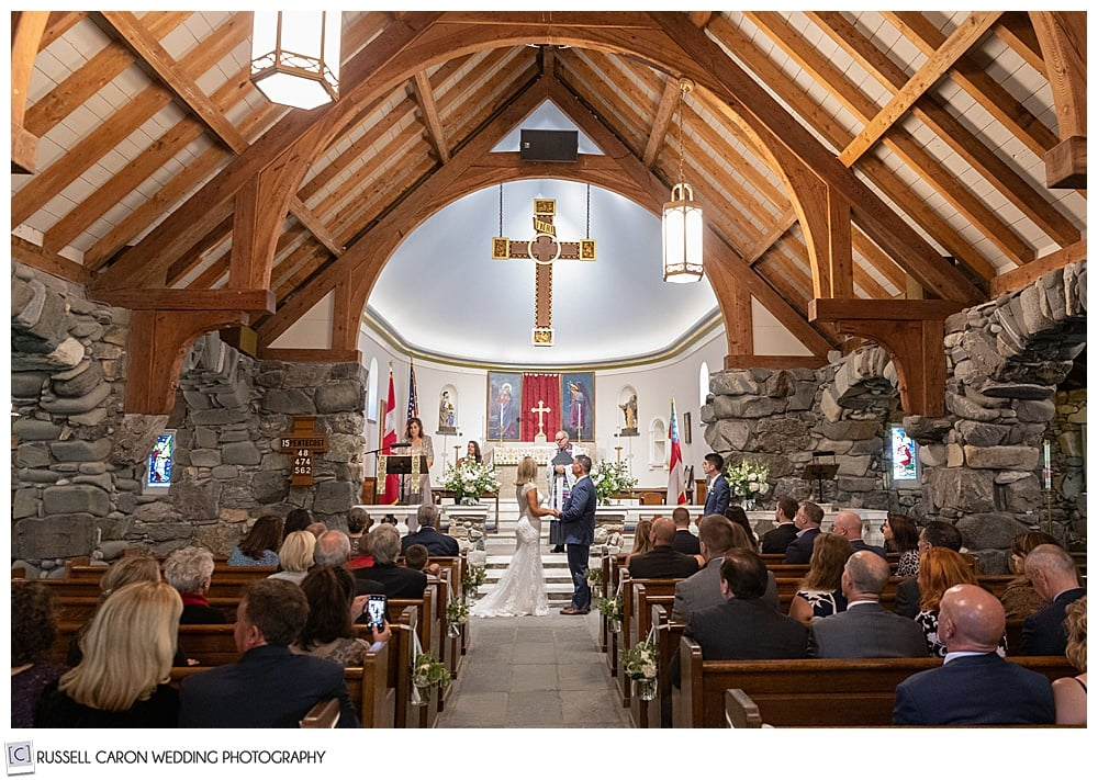 bride, groom, and congregation standing during a wedding ceremony at Saint Ann's Episcopal Church, Kennebunkport, Maine