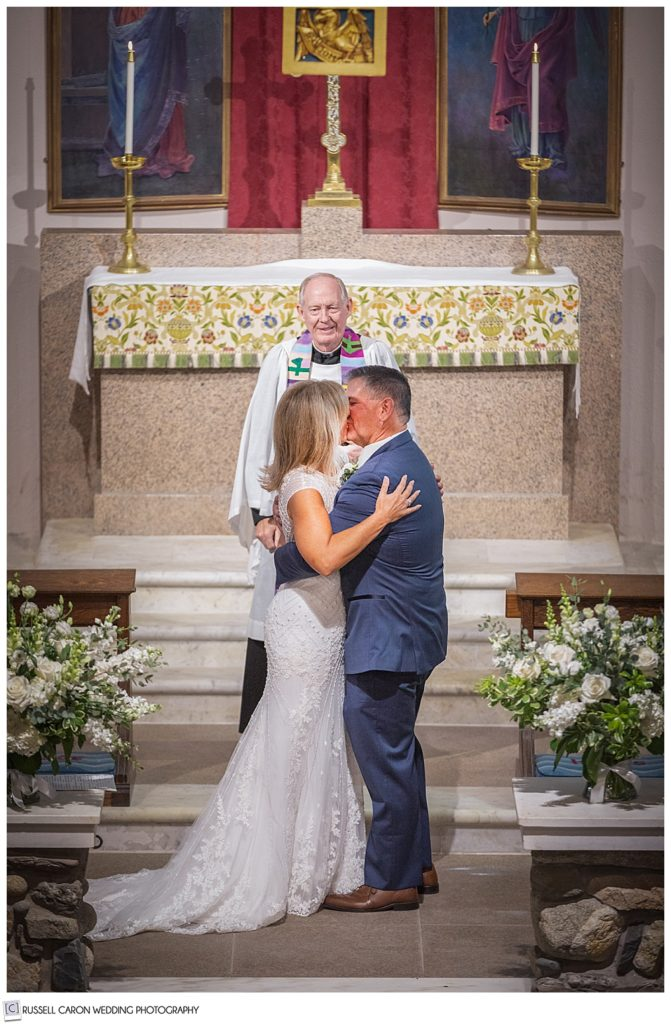 bride and groom's first kiss at the altar of Saint Ann's Episcopal Church, Kennebunkport, Maine