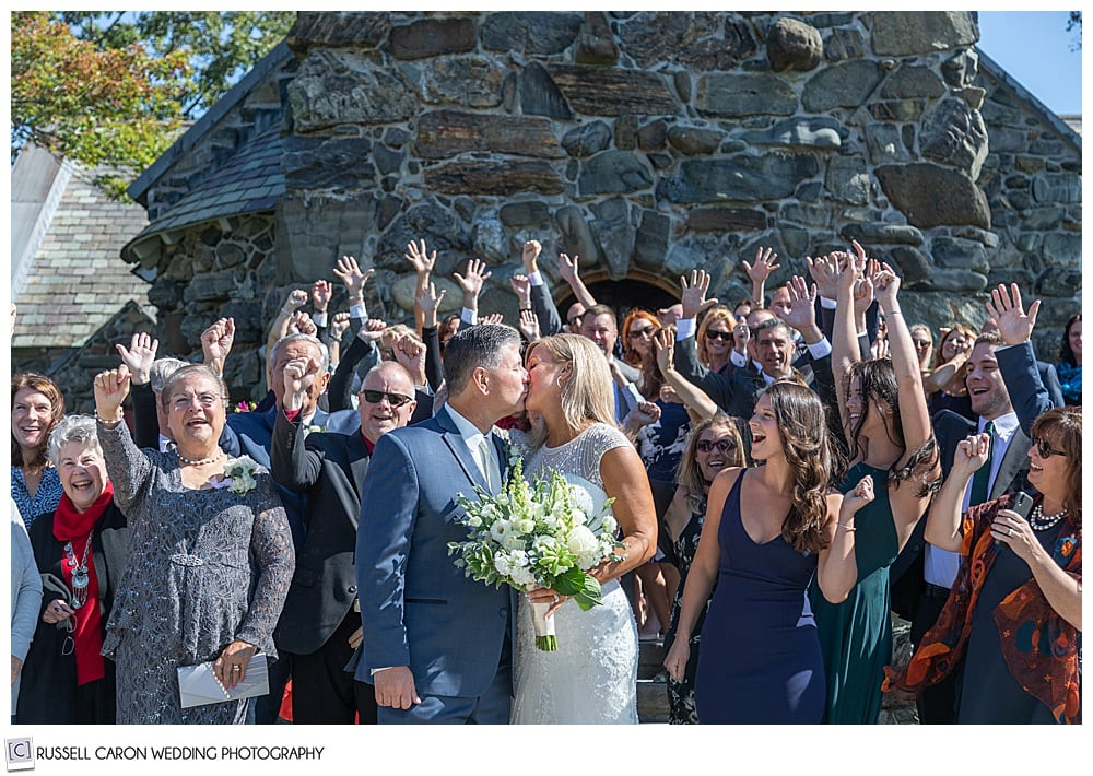 bride and groom kiss in front of Saint Ann's Episcopal Church in Kennebunkport, Maine, after their wedding ceremony