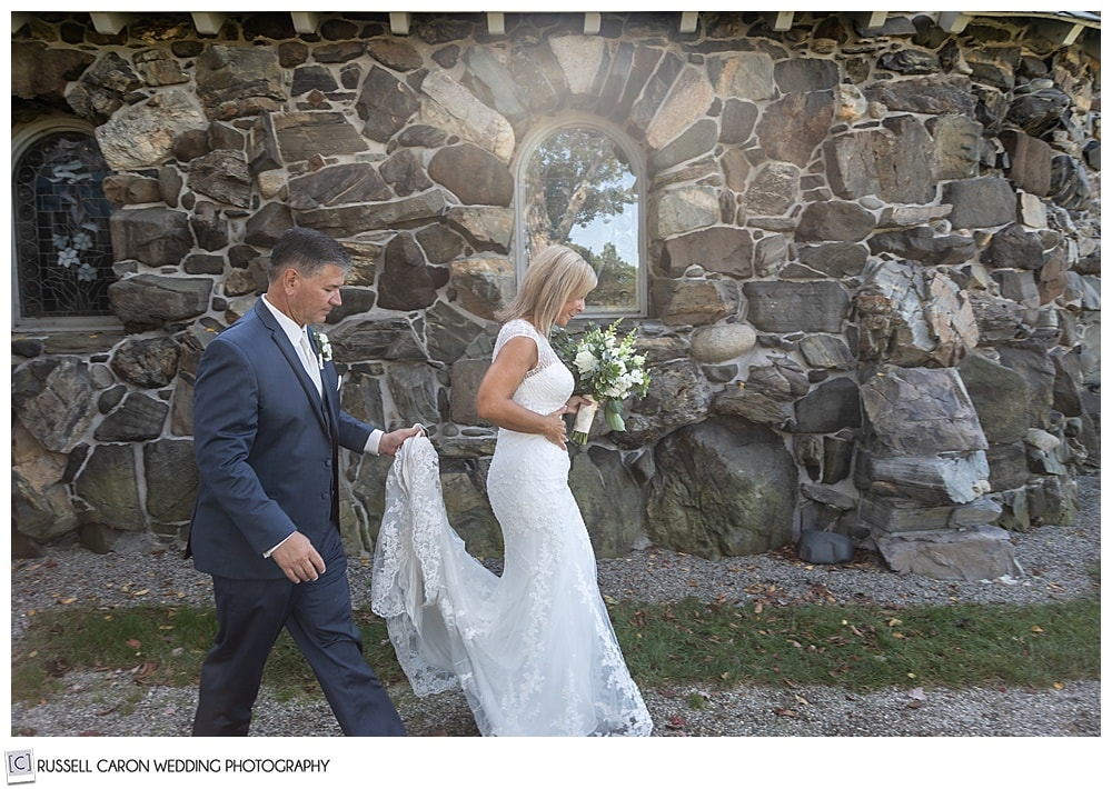 bride and groom walking past Saint Ann's Episcopal Church in Kennebunkport, Maine